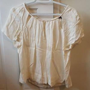 Cream colored drapey top with cutouts